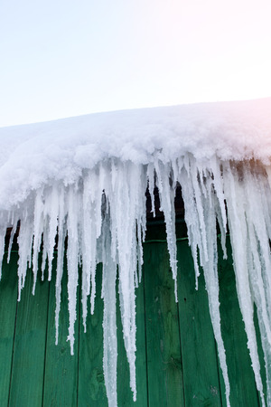 Icicles hang from the roof of the house Stock Photo