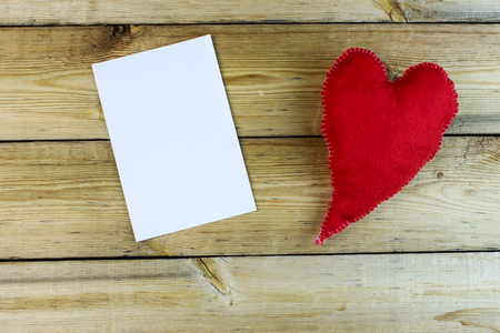 elongated: Fluffy elongated red heart, handmade with photo paper on an old wooden table