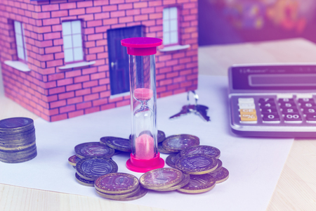 Hourglass house money and calculator on the table. The concept of time