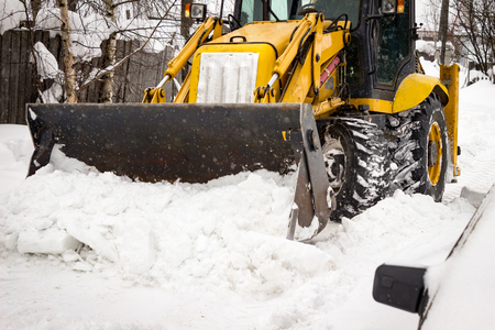plowing: Snow clearing. Tractor clears the road after snowfall