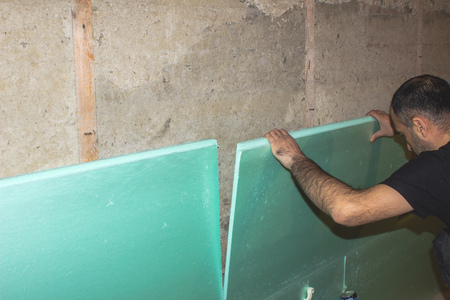 Builder insulates the walls inside the building. construction work