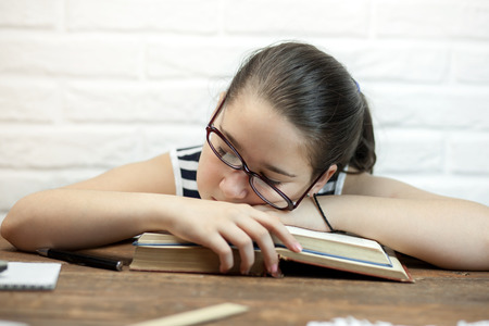A young student fell asleep at the table