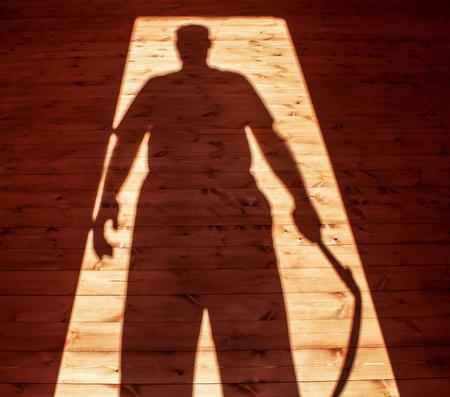 Shadow of man hand scythe
