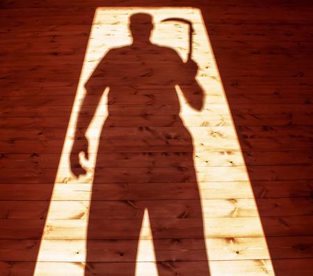 Man hand holding scythe in shadow 版權商用圖片