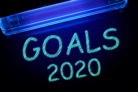 The word GOALS 2020 is manifested under the ultraviolet lamp in light blue Banco de Imagens