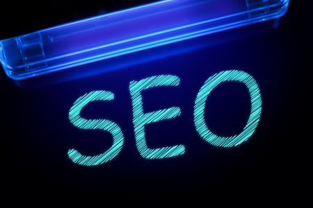 The word SEO is manifested under the ultraviolet lamp in light blue