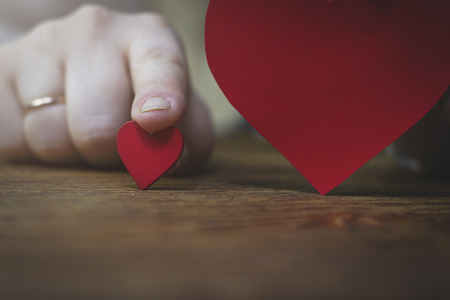 woman index finger holding a wooden red heart, which is next to the big heart Stock Photo