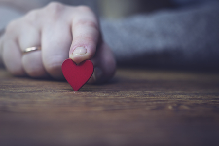 woman holding wooden red heart with index finger