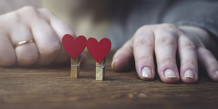 A woman sits with folded hands next to the clothes pegs with heart Stock Photo