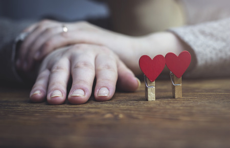 A woman sits with folded hands near the figure of a heart, close-up Stock Photo