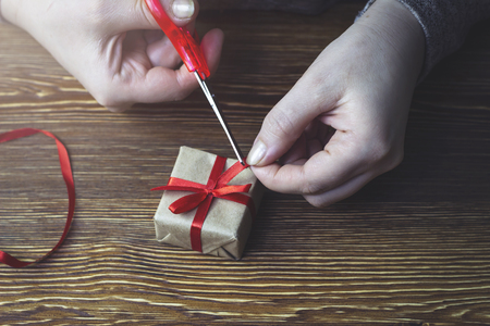 Woman cuts a red bow on a gift box Stock Photo