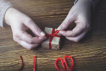 A woman ties a red bow on a gift box