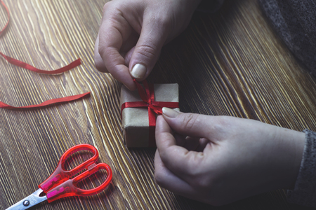 A woman ties a red bow on a gift box, close-up photo