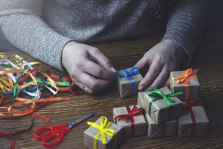 Woman tying bows on gifts, preparing for the holiday