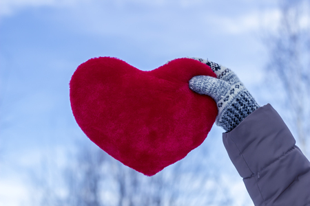 Woman holding a large heart with gloves on against the background of winter nature Stock Photo