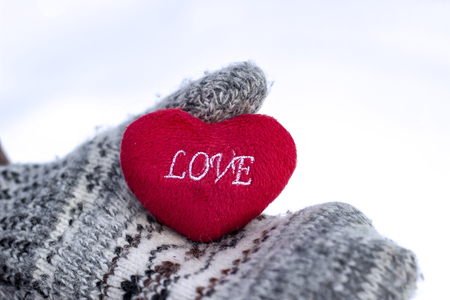 The girl in mittens holding a heart with the inscription LOVE