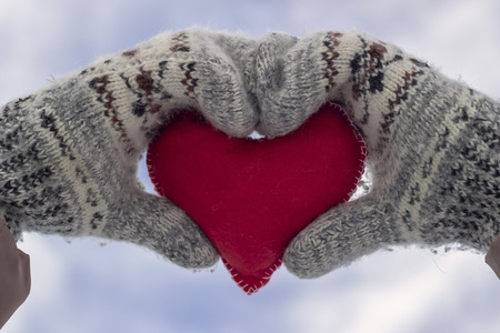 Girl holding a heart in mittens