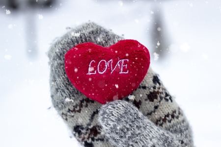 Woman holding a heart with the inscription LOVE in winter weather