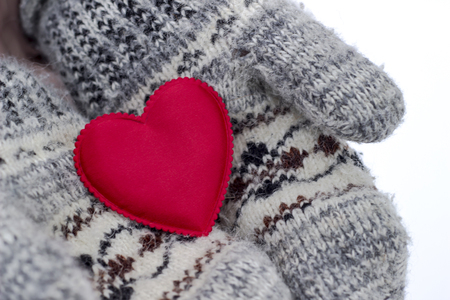 Woman holding a red heart in mittens in winter weather