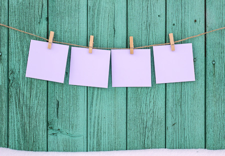 Four blank photos hanging on a clothespin rope Stock Photo