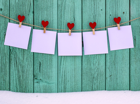 Five empty photos hanging on a rope clothespins with a heart