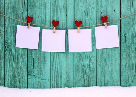 Four empty photos hanging on a rope clothespins with a heart