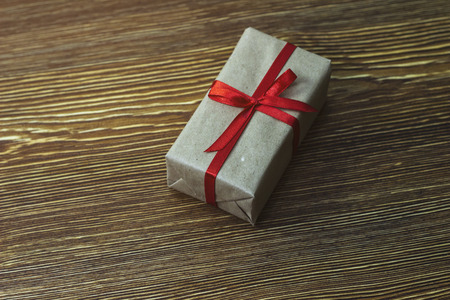 A gift box with a red ribbon is on a wooden table Stock Photo