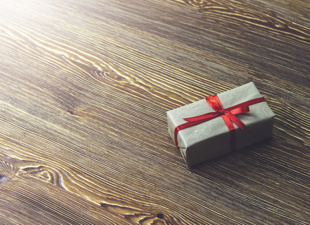 A gift box with a red ribbon is on a wooden table 版權商用圖片