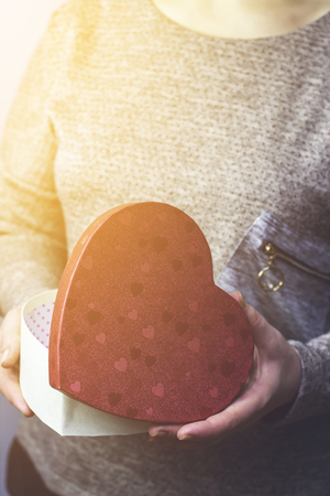 The girl opens a gift in the form of a heart
