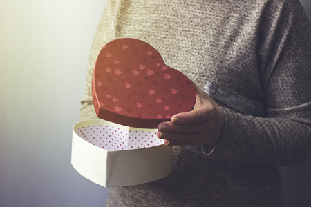 A woman opens a gift in the form of a heart, close-up Stock Photo