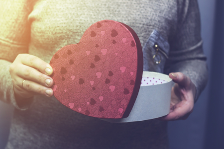 A woman opens a box in the form of a heart Stock Photo