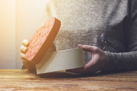 A woman opens a gift in the form of a heart Stock Photo