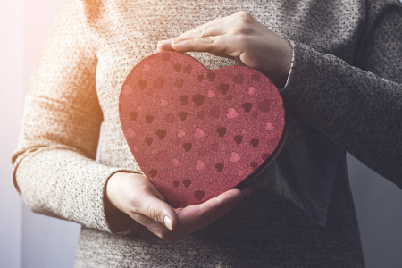Woman holding a gift box that looks like a heart