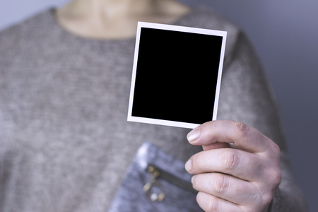 The woman holds in his hands a black photo Stock Photo