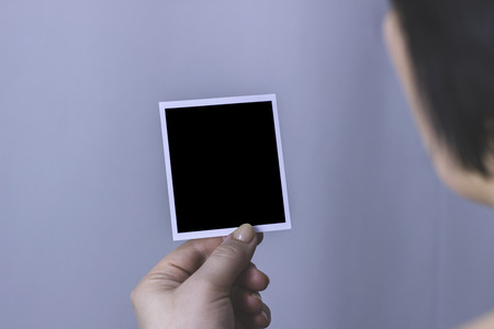 A woman looks at a blank black photo