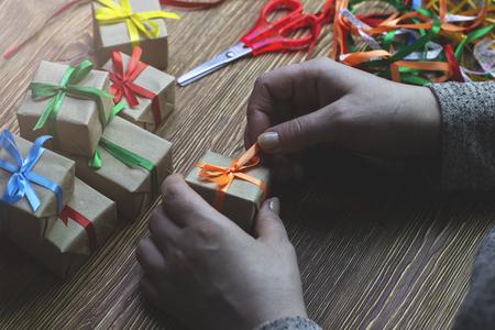 Woman tying a ribbon on a gift box