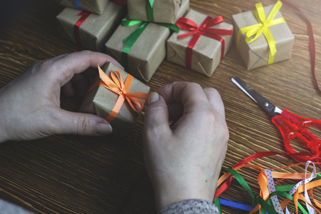 The girl is preparing for the holiday, tying a ribbon on the gift box
