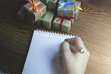 The girl writes in a notebook that lies next to the gifts