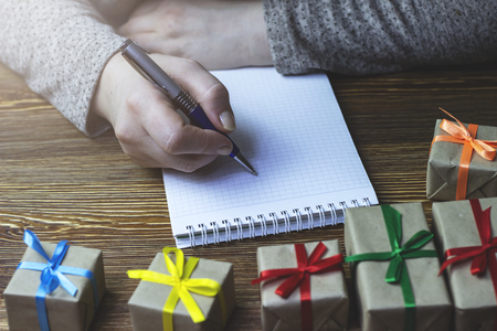 A woman makes a note in a notebook that lies on a wooden table Stock Photo