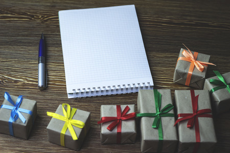 An empty notebook lies with a pen on a wooden table among the gifts