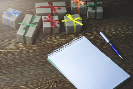 An empty notebook lying on a wooden table among the gifts