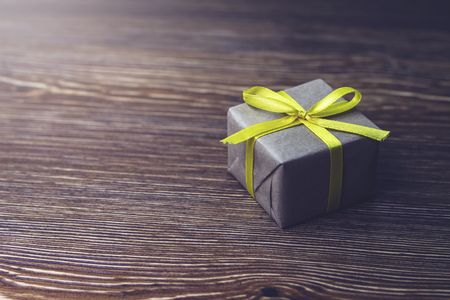 Gift box with yellow ribbon lying on a wooden table