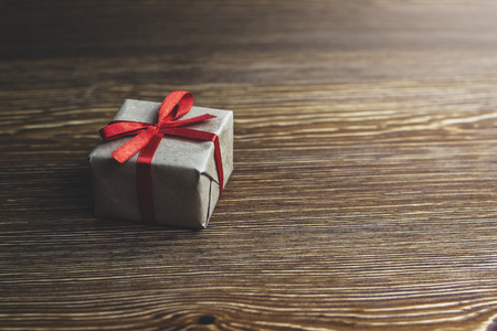 Gift box with red ribbon lying on a wooden table, side view Stock Photo