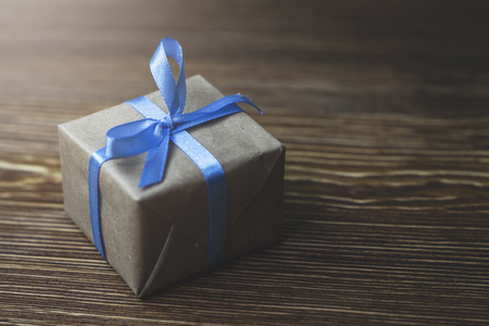 Gift box with blue ribbon lying on a wooden table, close-up