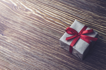 Gift box with red ribbon lying on a wooden table