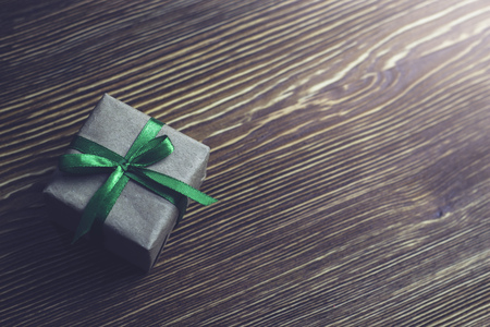 A gift box with a green ribbon lies on a wooden table
