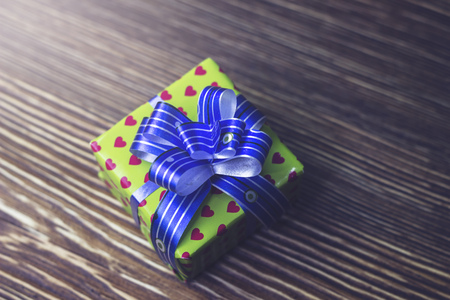Gift box is on a wooden table Packed in a beautiful wrapper with a blue ribbon