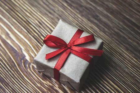 Gift box with red ribbon lying on a wooden table, close-up
