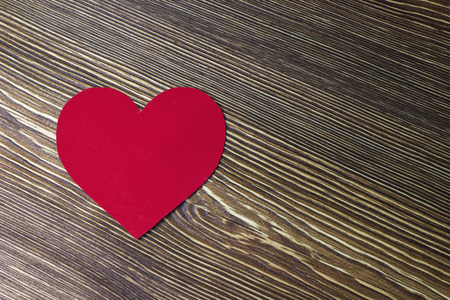 Paper red heart lies on a wooden table