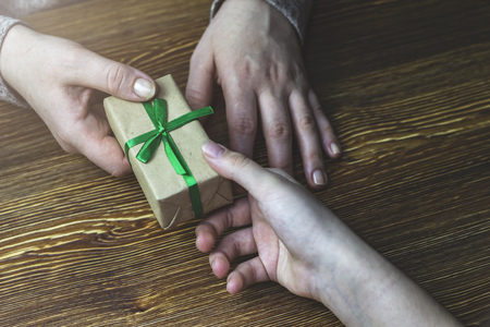 Girl gives a woman a gift box with a green ribbon Stock Photo